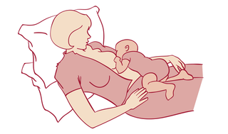 mother lying down with baby on top breastfeeding