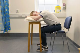 Physio sitting on chair leaning forward resting his elbows on a table. He is using a pillow for comfort.