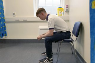 Physio sitting on chair leaning forward resting his elbows on his knees