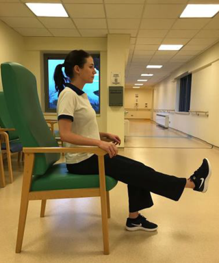 A woman sitting up straight on a chair. Her arms are on the armrests. One foot is on the floor. She is lifting one leg in parallel with the floor.