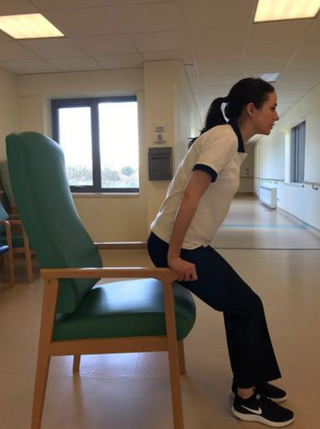 A woman standing up from a chair with her hands on the armrests.