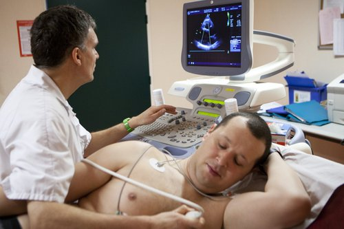 A cardiologist carrying out an echocardiogram on a patient