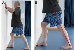 A man standing facing a wall with his legs apart, one foot in front of the other. One leg is bent forward at the knee with the foot touching the wall. The other leg is stretched out straight behind his body. He is pushing against the wall with his hands.