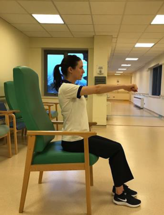A woman sitting up straight on a chair. Her feet are on the floor. She is holding her arms out in front of her in parallel with the floor.